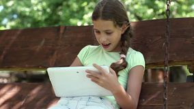 Den nätta flickan med minnestavladatoren sitter på gungabänken stock video