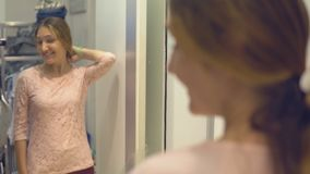 Den nätta flickan ser hennes reflexion i spegeln, medan försöka på kläder i modelager, medan shoppa lager videofilmer