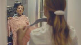 Den nätta flickan ser hennes reflexion i spegeln, medan försöka på kläder i modelager, medan shoppa arkivfilmer