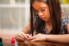 Den nätta flickan som målar henne, spikar Royaltyfri Foto