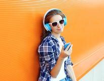 Den nätta flickan tycker om lyssnar till musik i hörlurar arkivfoto