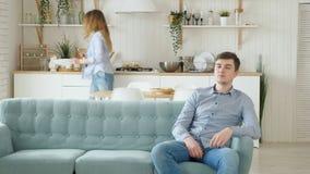 Den nätta frun lägger tabellmaken sitter på hållande ögonen på TV för soffan lager videofilmer
