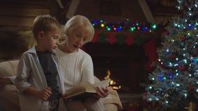 Den nätta gamla damen läser en saga till hennes sonson i julnatt arkivfilmer