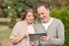 Den nätta gamla maken och frun använder en minnestavla royaltyfria bilder