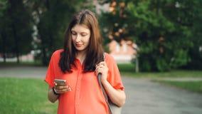 Den nätta gravida kvinnan använder smartphonen som ser skärmen som in går, parkerar på sommardag Modern teknologi som är sund lager videofilmer