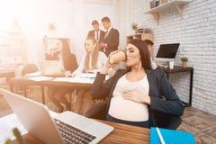 Den nätta gravida kvinnan dricker koppen kaffe på arbetsplatsen Den gravida flickan rymmer hennes gravida buk Arkivbilder