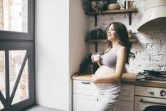 Den nätta gravida kvinnan i kök med koppen av mjölkar royaltyfria foton