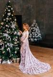 Den nätta gravida kvinnan med blont fantastiskt lockigt propert hår som bär ett vitt, snör åt den genomskinliga ljusa klänningen  royaltyfri foto