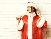 Den nätta gulliga santa flickan eller att le brunettkvinnan i tröja för nytt år och jul eller xmas-hatt rymmer det rosa piggy svi royaltyfria bilder