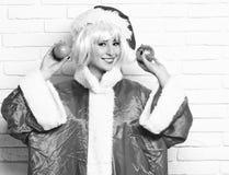 Den nätta gulliga sexiga santa flickan eller att le brunettkvinnan i röd tröja för nytt år och julhatten i rosa peruk rymmer xmas arkivfoto