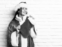 Den nätta gulliga sexiga santa flickan eller att le brunettkvinnan i tröja för nytt år och jul eller xmas-hatt rymmer dekorativt royaltyfri bild