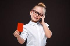 Den nätta gulliga unga flickan i den vita skjortan och den svarta byxan rymmer det röda kortet och talar på telefonen Fotografering för Bildbyråer