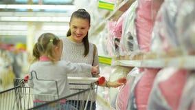 Den nätta härliga modern med mörkt hår visar rosa färgkudden för hennes dotter som står den near supermarkethyllan med stock video