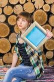 Den nätta kort-haired flickan sitter på en bänk och rymmer en ram med stället för text på en bakgrund av träjournaler royaltyfri bild