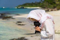 Den nätta kvinnan är en fotograf med slrkameran Arkivfoto