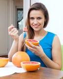 Den nätta kvinnan äter grapefrukten Arkivfoton