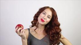 Den nätta kvinnan biter det röda nya äpplet i den vita studion lager videofilmer