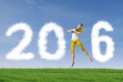 Den nätta kvinnan hoppar på fältet med nummer 2016 Fotografering för Bildbyråer