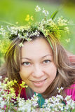 Den nätta kvinnan i en krans från blommor i sol strålar Fotografering för Bildbyråer