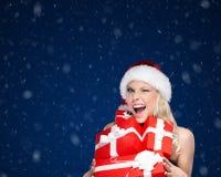 Den nätta kvinnan i jullock rymmer en uppsättning av gåvor royaltyfri bild