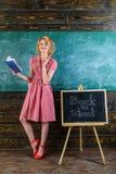 Den nätta kvinnan läste akademisk litteratur i klassrum Läraren är tillbaka till skolan som studerar engelskt språk och litteratu royaltyfri bild