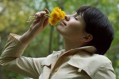 Den nätta kvinnan luktar blommorna i parkera Arkivfoto