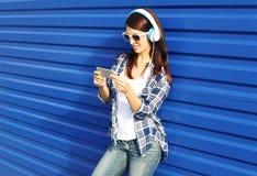 Den nätta kvinnan lyssnar till musik i hörlurar och användasmartphonen Royaltyfri Foto