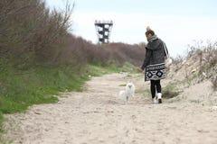 Den nätta kvinnan med hennes hund ut i parkerar Valpen som den vita hunden kör med det, är ägaren royaltyfri fotografi