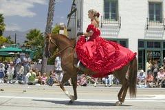 Den nätta kvinnan med röd spanjor klär på hästrygg under invigningsdag ståtar ner State Street, Santa Barbara, CA, gammal spansk  Arkivbilder