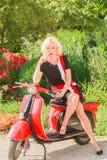 Den nätta kvinnan på en sparkcykel tänker royaltyfri bild