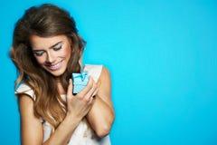 Den nätta kvinnan räcker en gåvaask som isoleras på blått Arkivfoto