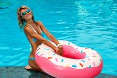 Den nätta kvinnan simmar på en uppblåsbar cirkel royaltyfri fotografi