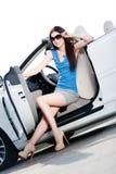 Den nätta kvinnan sitter i bilen med den öppnade sidodörren royaltyfri foto