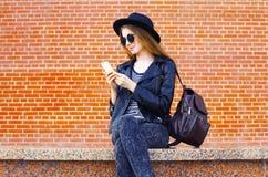Den nätta kvinnan som använder smartphonen vaggar in, svart stil över tegelstenar Royaltyfri Foto