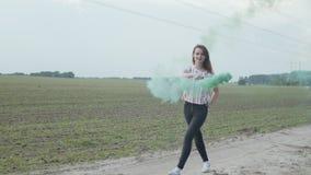 Den nätta kvinnan som går på den dammiga vägen med rök, bombarderar
