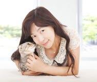 Den nätta kvinnan som ler och, kramar hennes katt Royaltyfria Bilder