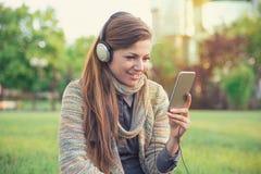 Den nätta kvinnan som lyssnar till musik parkerar in royaltyfri foto