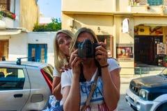 Den nätta kvinnan som tar ett fotografi av henne i en spegel av, ställer ut royaltyfri bild