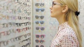 Den nätta kvinnan väljer sol- exponeringsglas i optikerlager lager videofilmer