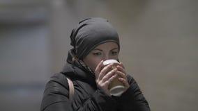 Den nätta kvinnan värme och varmt kaffe för drink i tunnelen, vinter lager videofilmer