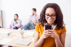 Den nätta kvinnliga arbetaren använder en telefon Royaltyfria Bilder