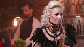 Den nätta kvinnliga saxofonisten i svart fjäderetappdräkt utför i en restaurang arkivfilmer