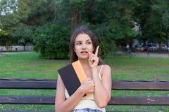 Den nätta kvinnliga studenten rymmer en bok och tänker om något Kvinnan har en intressant idé fotografering för bildbyråer