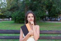 Den nätta kvinnliga studenten rymmer en bok och tänker om något Kvinnan har en intressant idé royaltyfria foton
