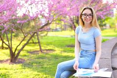 Den nätta kvinnliga studenten som vilar och studerar, i att blomma, parkerar royaltyfri bild