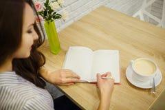 Den nätta le kvinnan gör tillträdeet i hennes dagbok på tabellen royaltyfria bilder