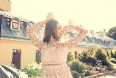 Den nätta le modellen snör åt in klänningen som poserar på gatan i strålar Royaltyfri Foto