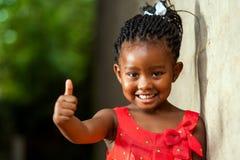 Den nätta lilla afrikanska flickavisningen tummar upp. Royaltyfri Foto