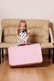 Den nätta lilla blonda flickan släpar den stora rosa resväskan nära soffan Royaltyfri Bild