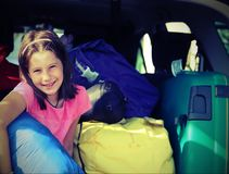 Den nätta lilla flickan fyller resväskorna på bilen med tappning Royaltyfri Bild